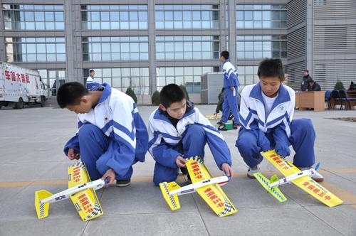 电动线操纵模型飞机的学生们在做赛前准备
